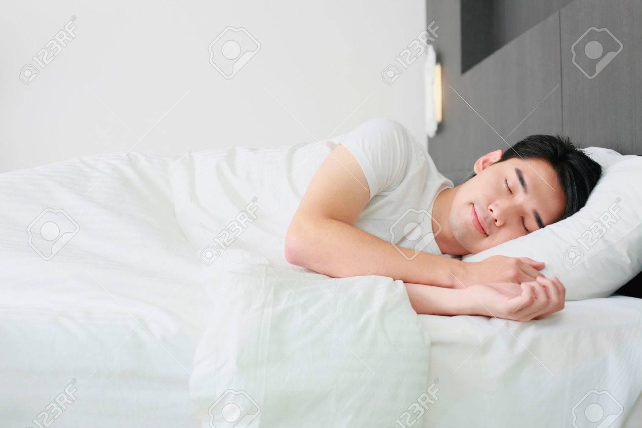 Man sleeping on bed Stock Photo - 26386439