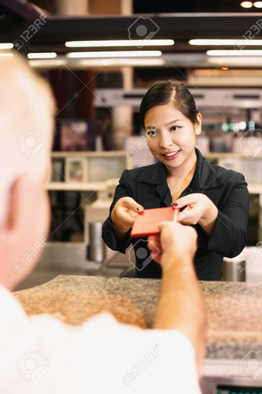 Airline check-in attendant returning businessman's passport at the airport check-in counter Stock Photo - 26386670