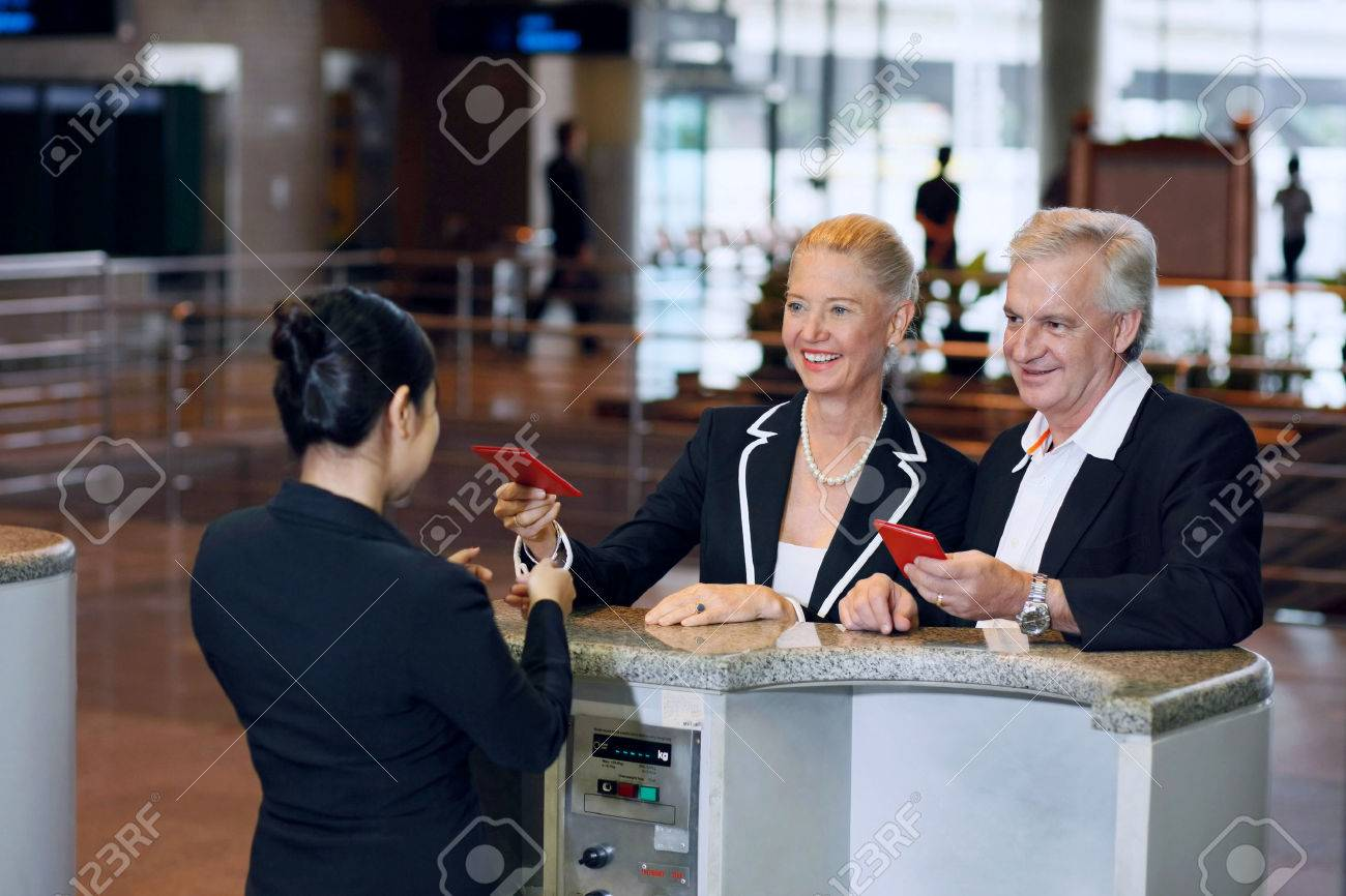 Businessman and businesswoman at the airport check-in counter with their passports Stock Photo - 26386685