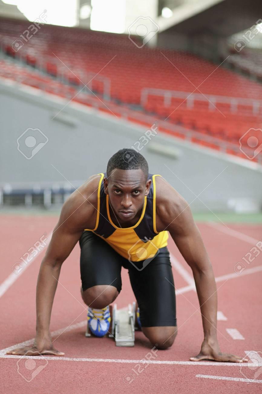 Male runner crouching on starting line Stock Photo - 26388743