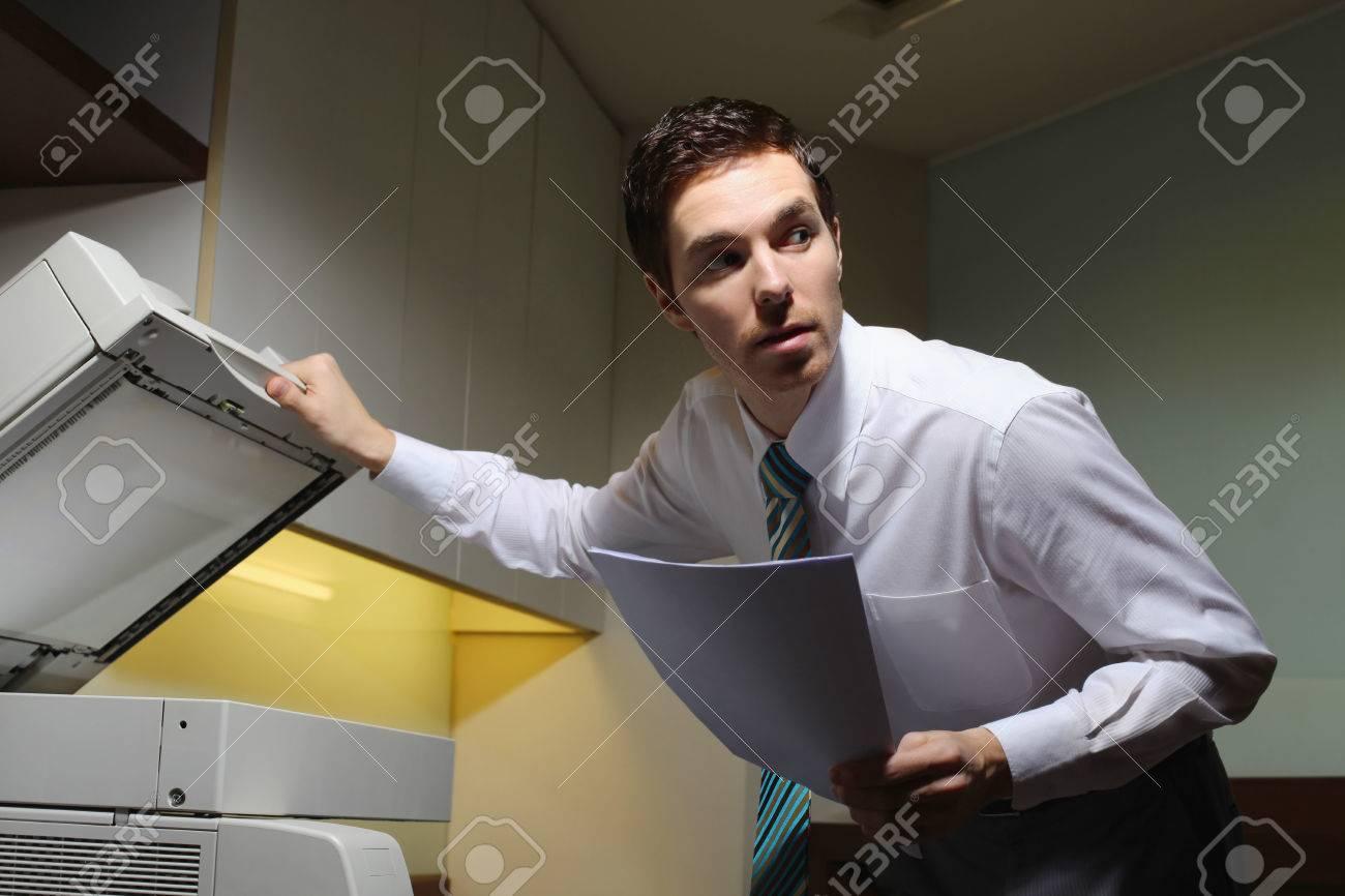 Businessman secretly copying documents Stock Photo - 26388851