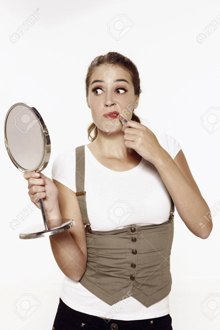 woman holding hand mirror. Woman Holding Hand Mirror While Applying Lipstick Stock Photo - 26391496