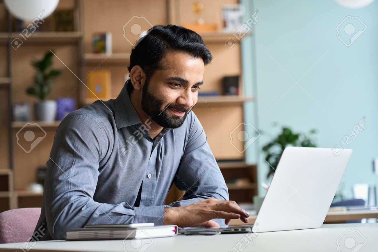 Smiling indian business man working studying on laptop computer at home office. - 166242553