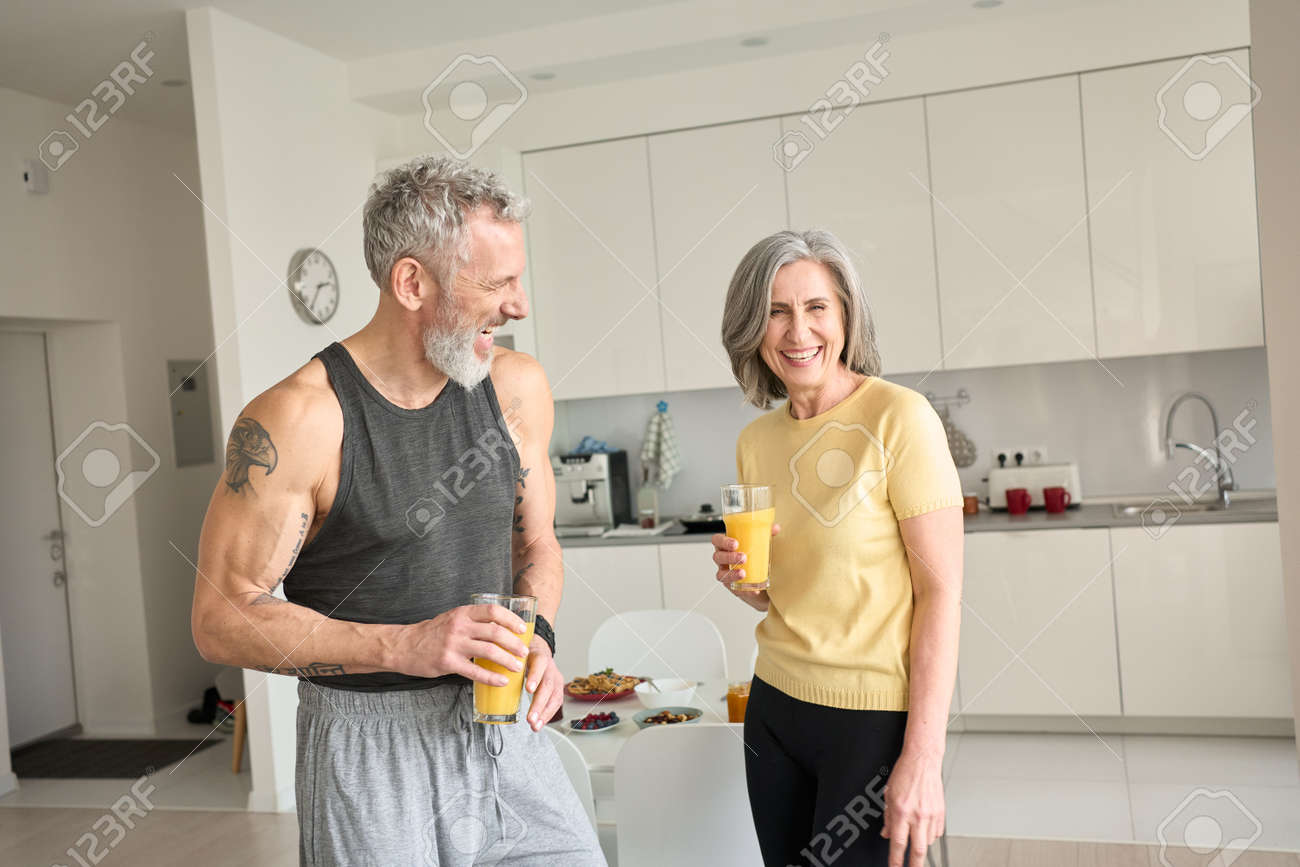 Healthy sporty happy seniors family couple drinking juice and laughing at home. - 168869512