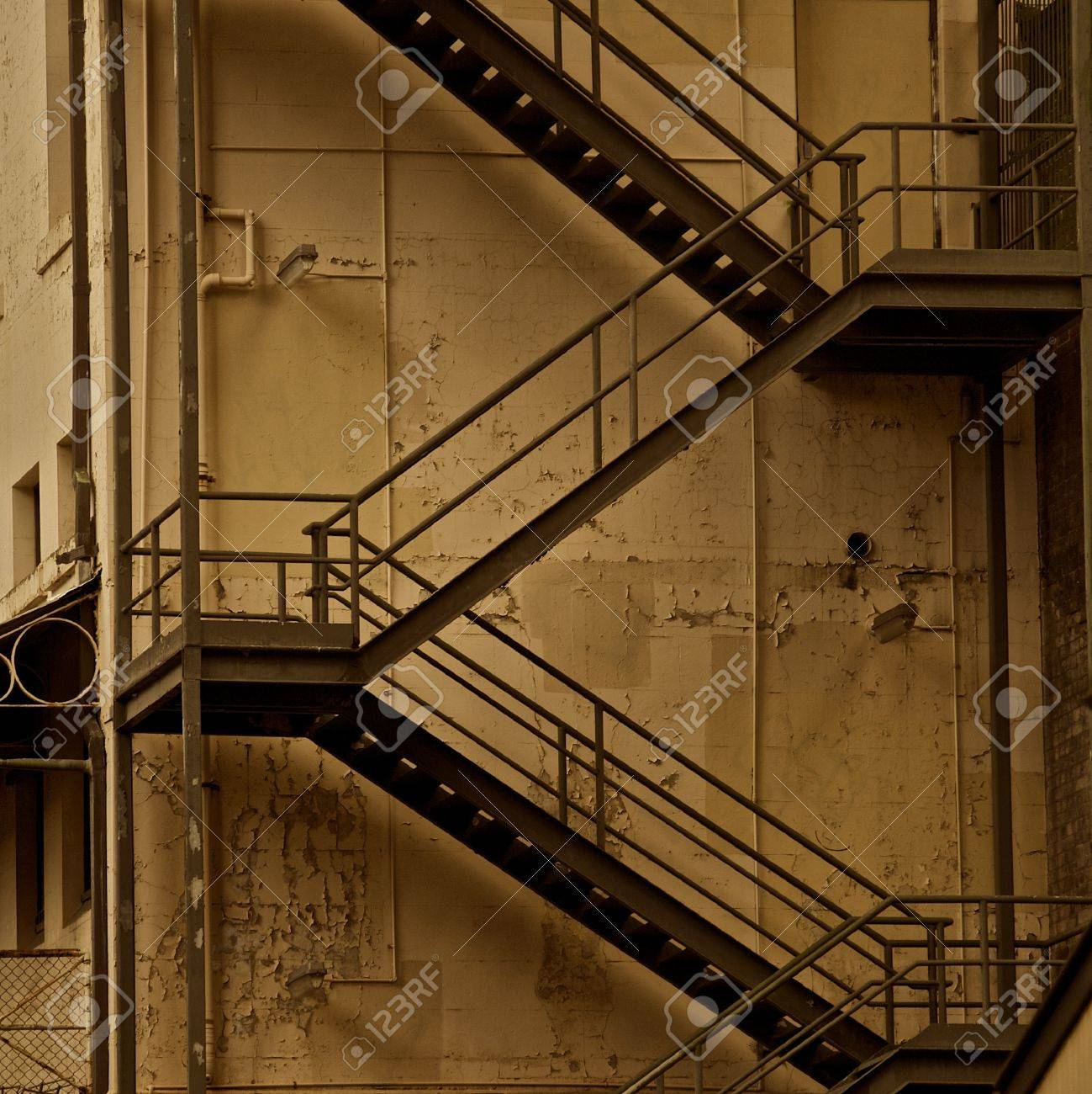 Metal Fire Escape Stairs on the Side of a Textured Building Sepia - 13828525