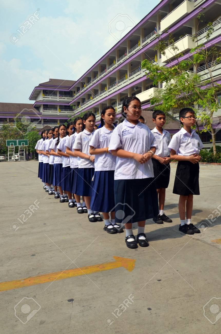 Students stand in line with the school building as a backdrop - 22625874