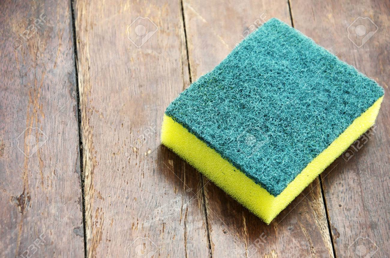 Dishwashing sponge with a wooden floor in the background. - 51332304