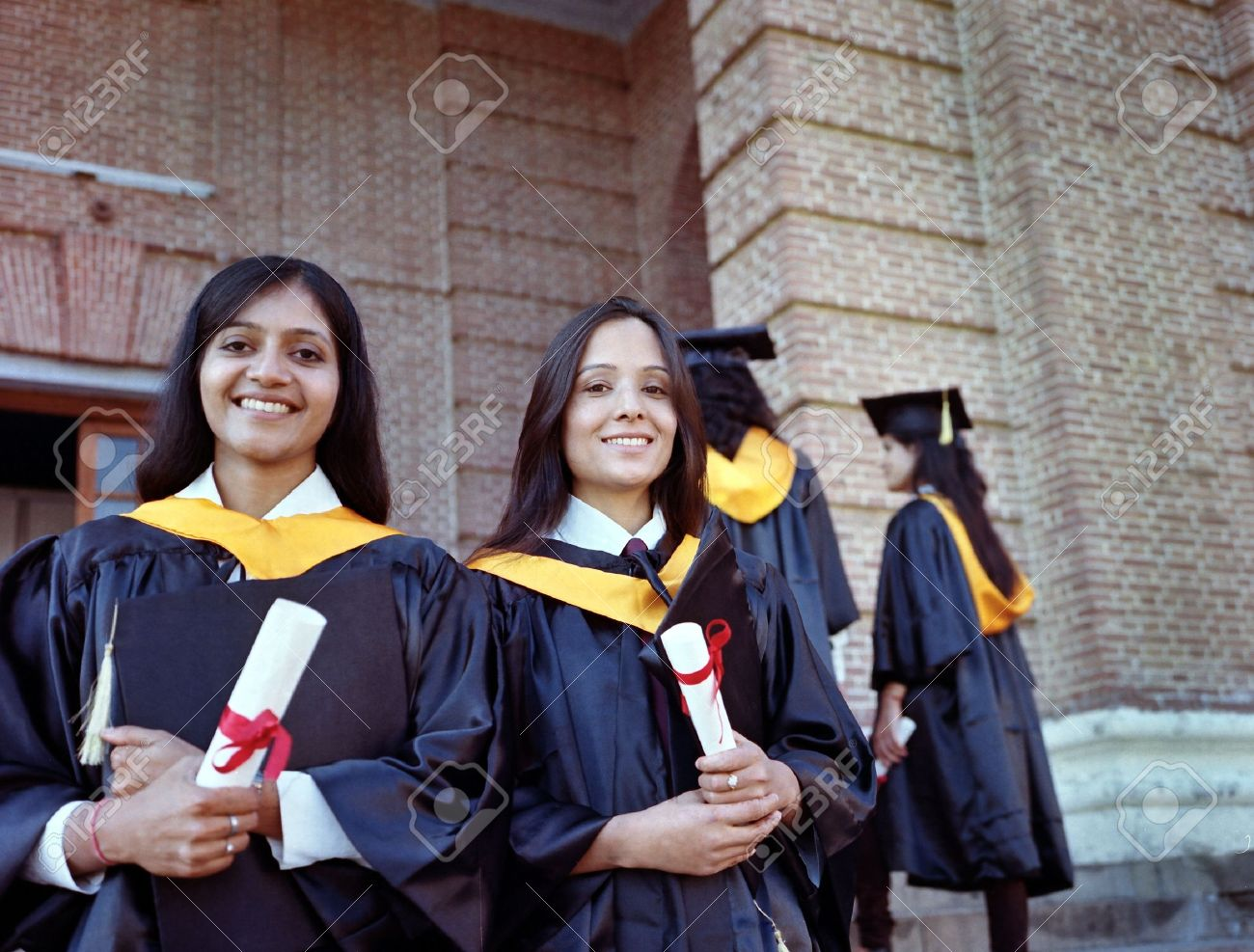 two pretty n college graduates happy after getting degree stock photo two pretty n college graduates happy after getting degree in the campus