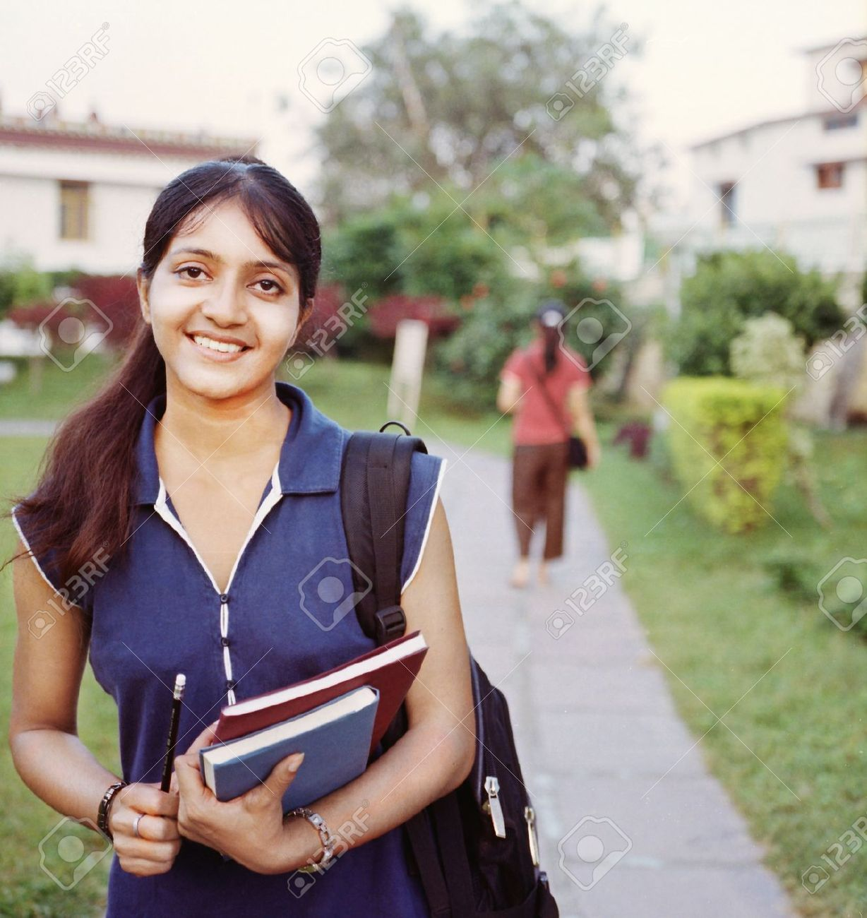 happy indian college student walking in the campus, with books