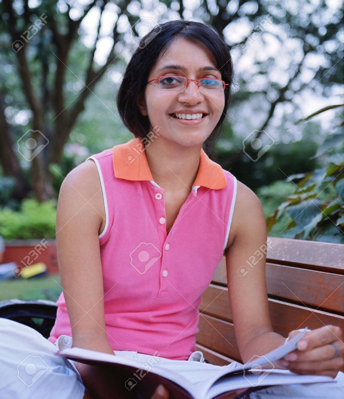 cute indian college student sitting on a bench and reading a.. stock