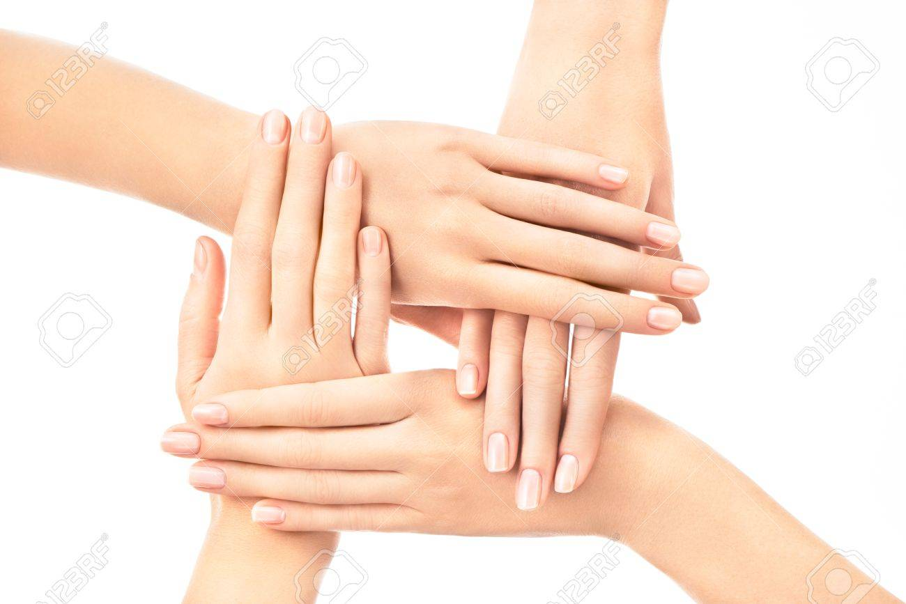 Four female hands placed one over another with french nail design on white  background Stock Photo - Four Female Hands Placed One Over Another With French Nail Design