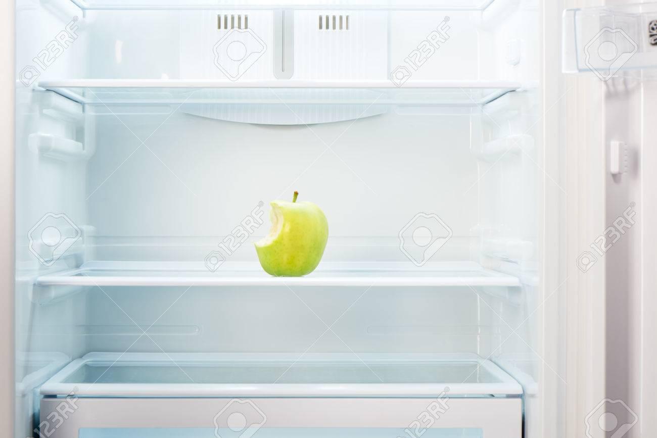 Kühlschrank Regal : Grüner apfel gebissen auf dem regal der offenen leeren kühlschrank