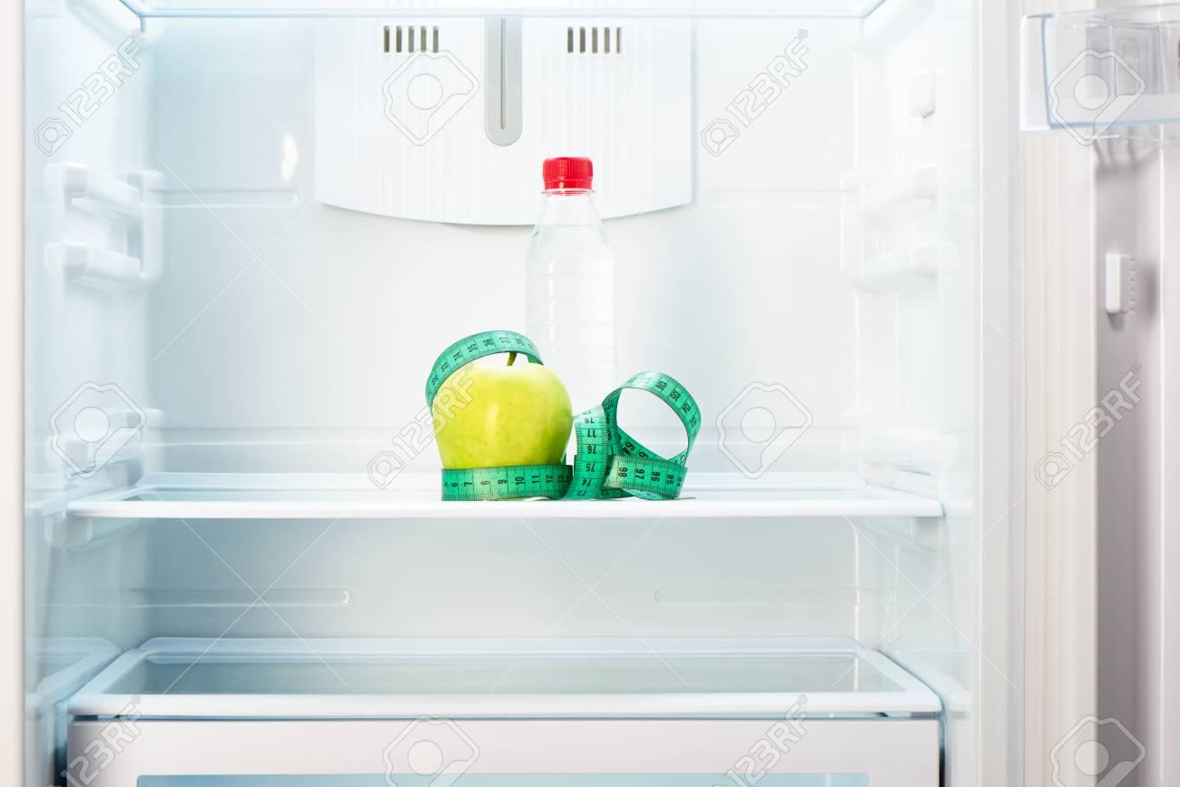 Kühlschrank Regal : Flasche wasser mit maßband auf dem regal der offenen leeren