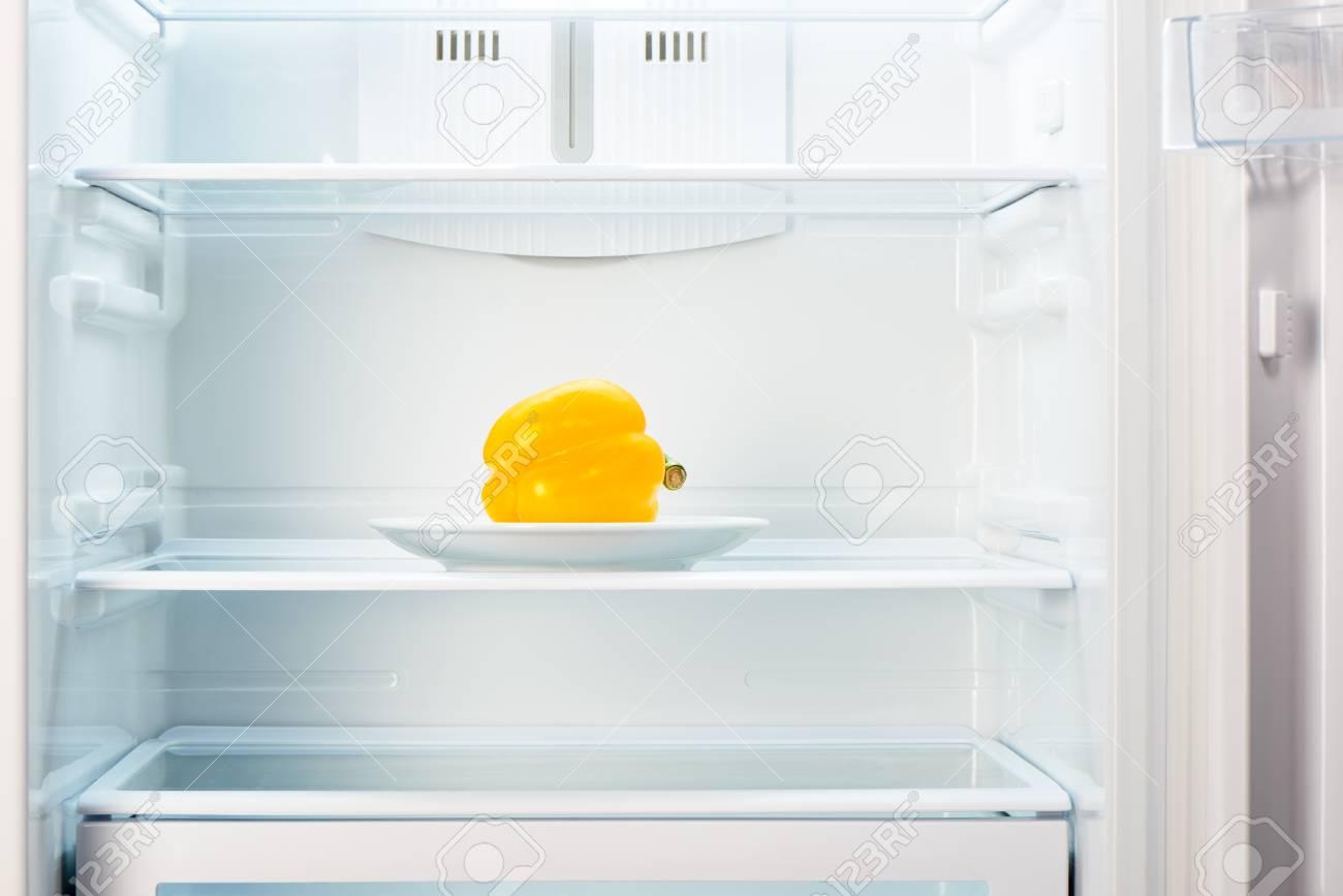 Kühlschrank Platte : Gelber pfeffer auf weißer platte im offenen leeren kühlschrank