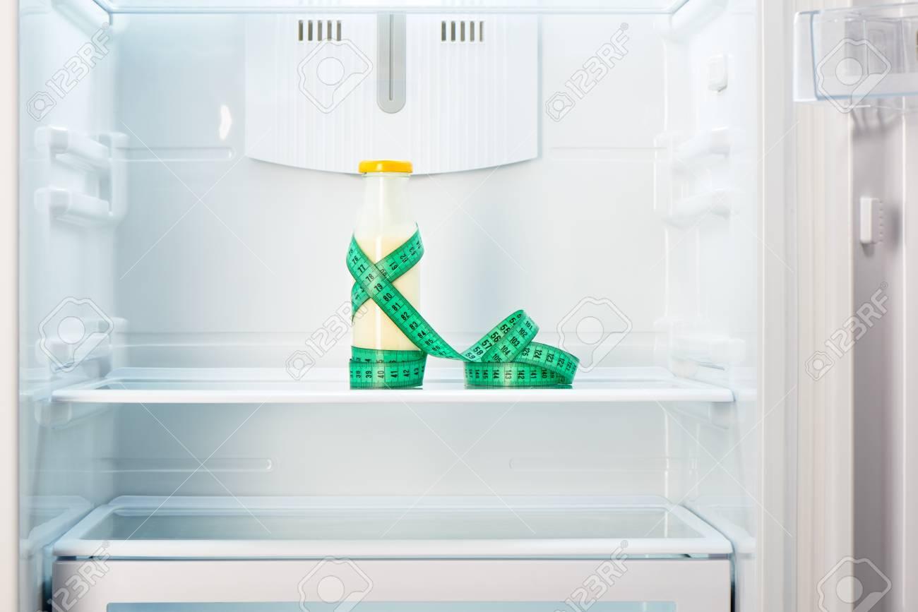 Kühlschrank Regal : Glasflasche von joghurt mit maßband auf dem regal der offenen leeren
