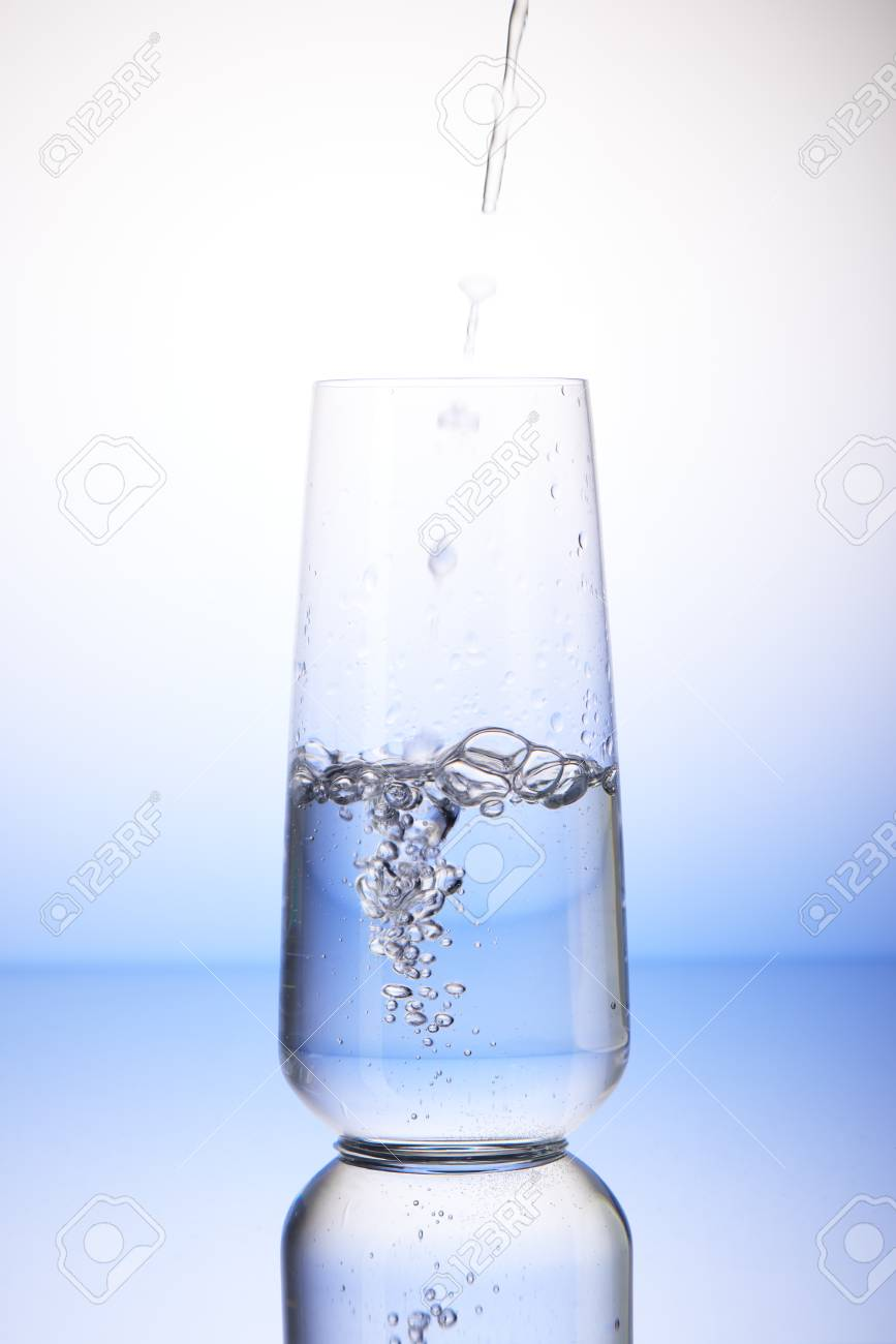 427781c289b Water pouring into half-filled drinking glass with reflection on white and  blue background Stock