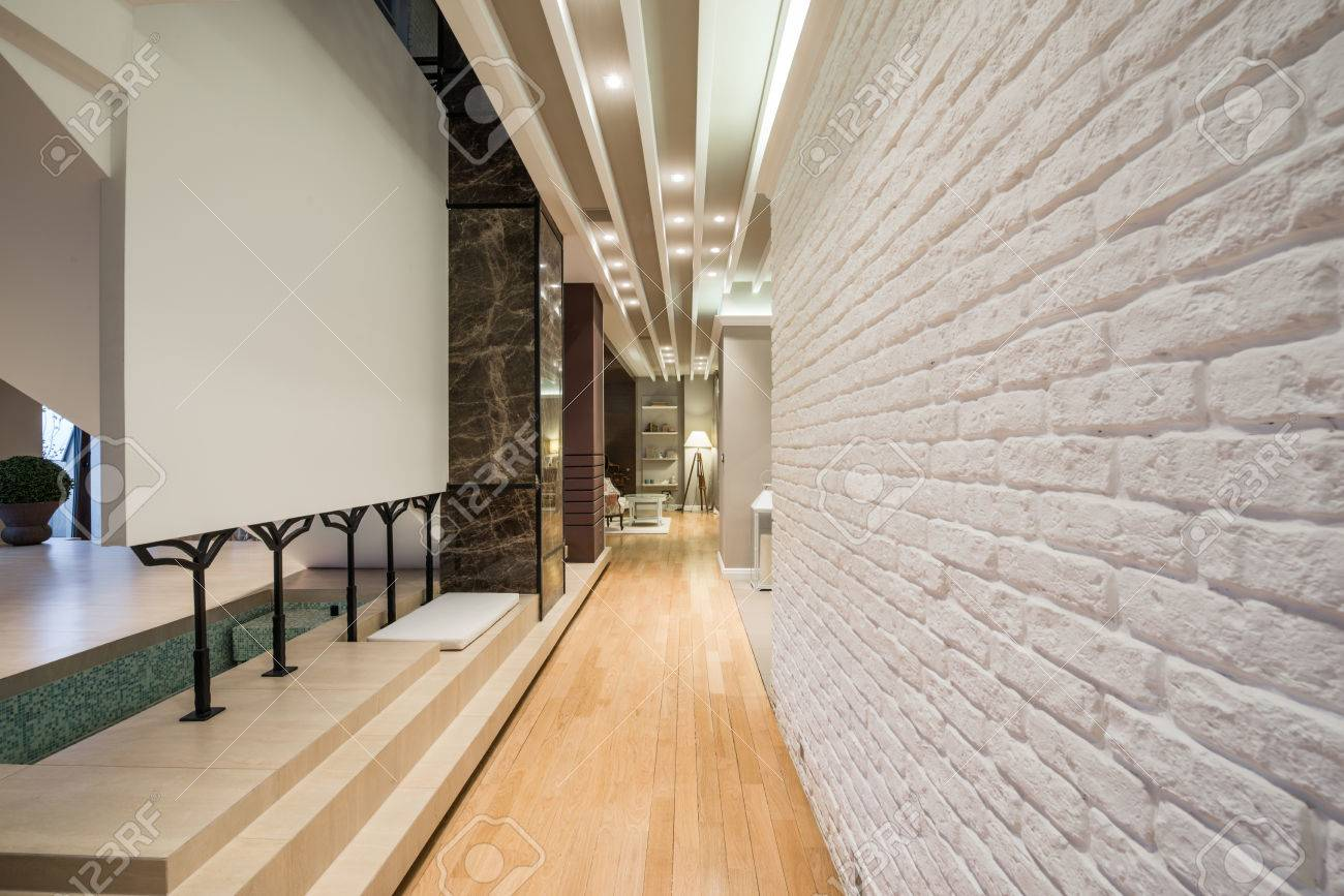Interior of a long corridor with white brick wall stock photo