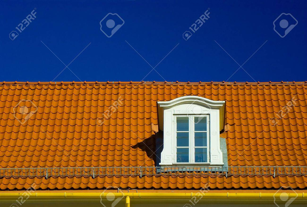 Dormer roof window, in a flashing orange tiled roof on blue sky Stock Photo - 739812