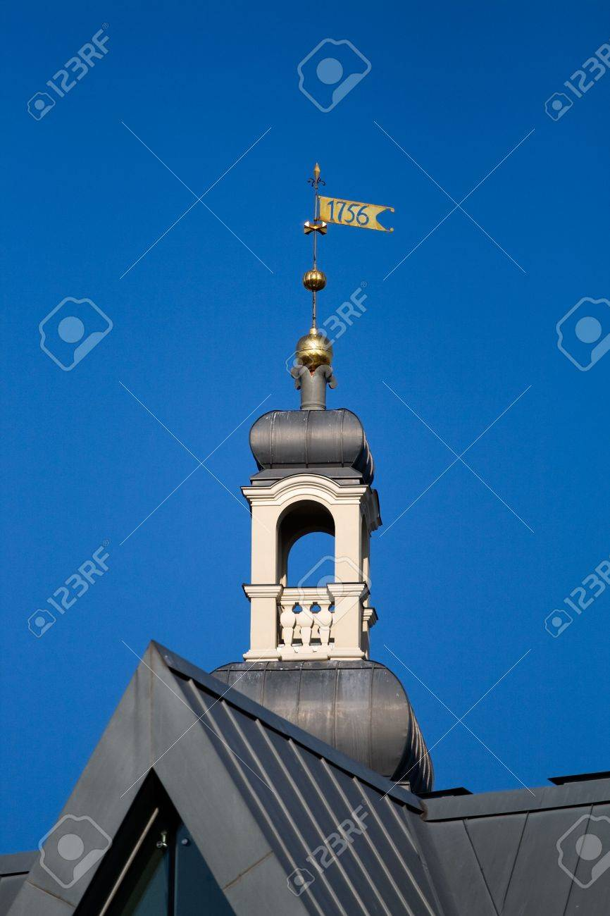 Small turret with metalic weather vane of Riga city hall against blue sky Stock Photo - 5522529