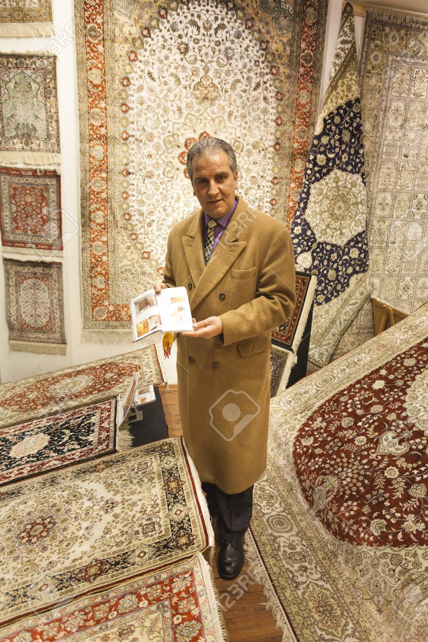 Banque d images - ISTANBUL, TURQUIE - 19 mars 2011  Unidentified vendeur de  tapis offrant des tapis orientaux colorés à son magasin au cours des essais  de ... ff0670eefb8