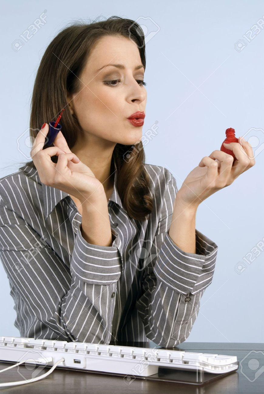 Businesswoman applying nail polish, blowing, close-up Stock Photo - 23853475