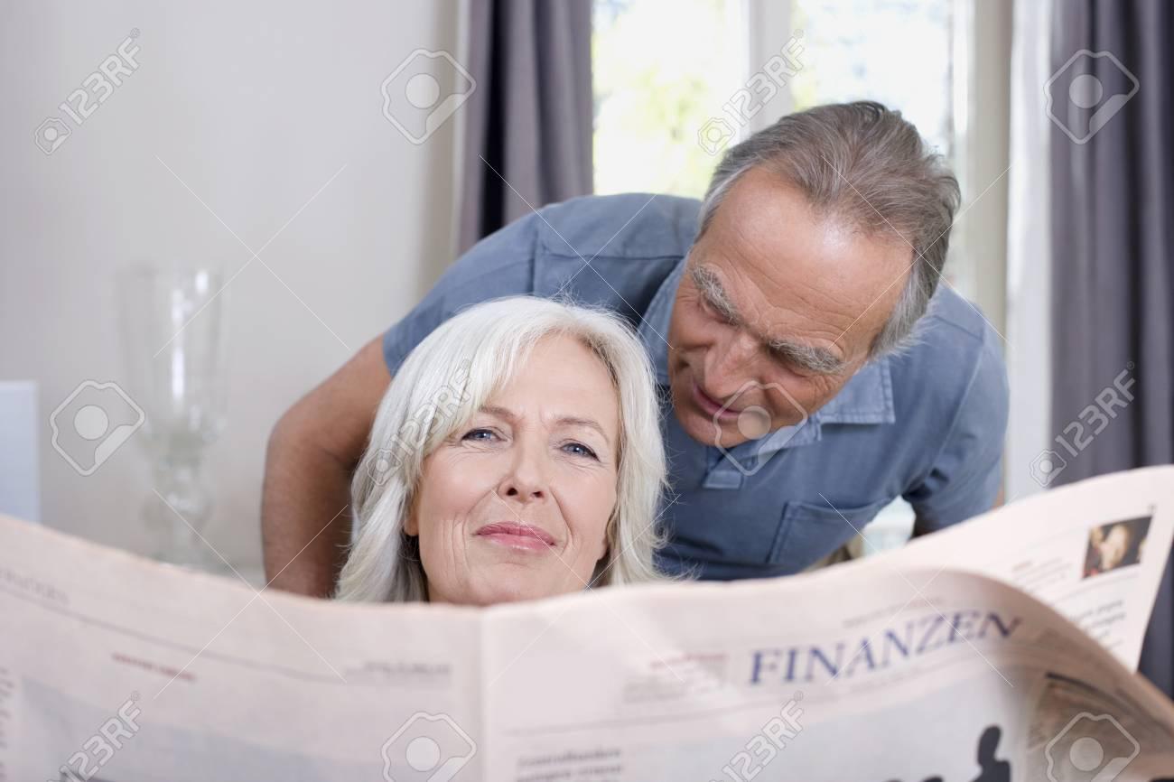 Senior Woman holding a newspaper, senior man behind, portrait Stock Photo - 23891438