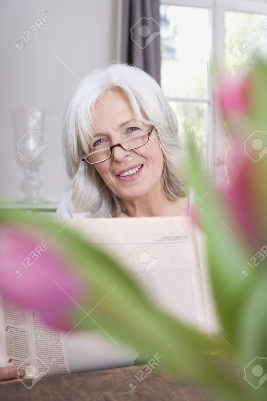 Senior woman holding newspaper, smiling, portrait Stock Photo - 23891441