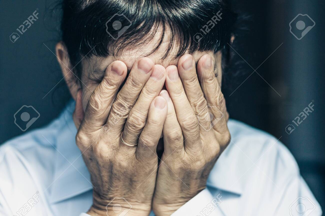 Sad depressed, stressed, thoughtful, senior, middle aged old woman, gloomy, worried, covering her face. Human expressions, emotion, feelings and reaction - 135523498