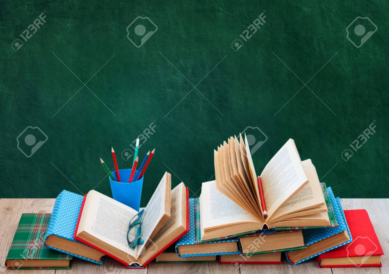 Back to school, pile of books in colorful covers and on wooden table with empty green school board background. Distance home education.Quarantine concept of stay home - 154014044