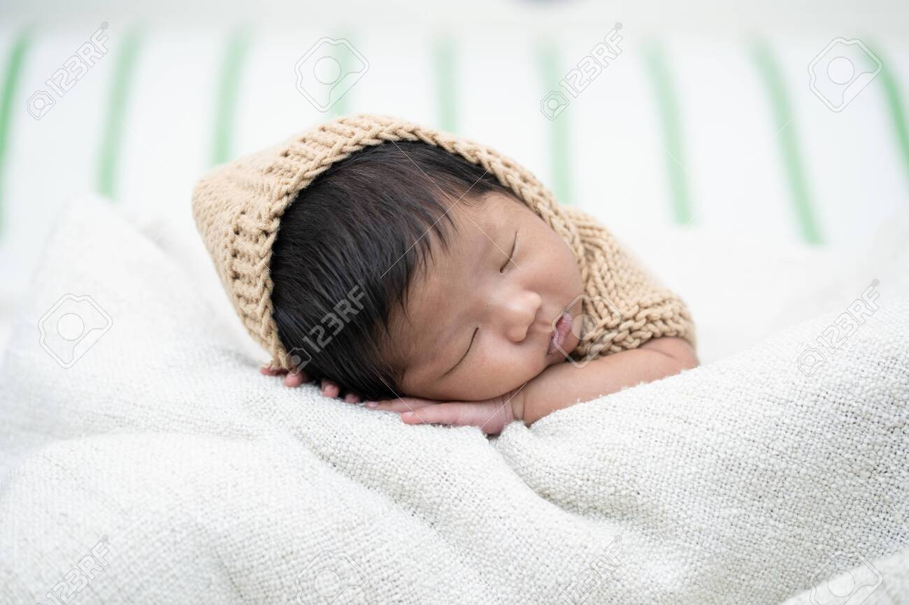 Adorable newborn baby peacefully sleeping on a white blanket. - 138443035