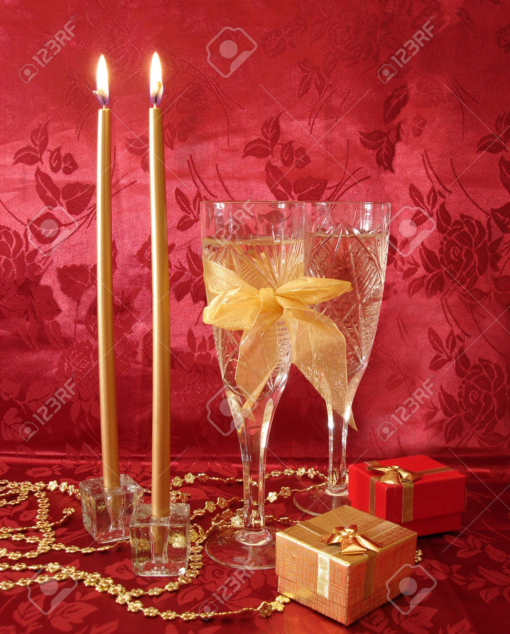 Two wine glasses with champagne, gifts and golden candles on red background Stock Photo - 763763