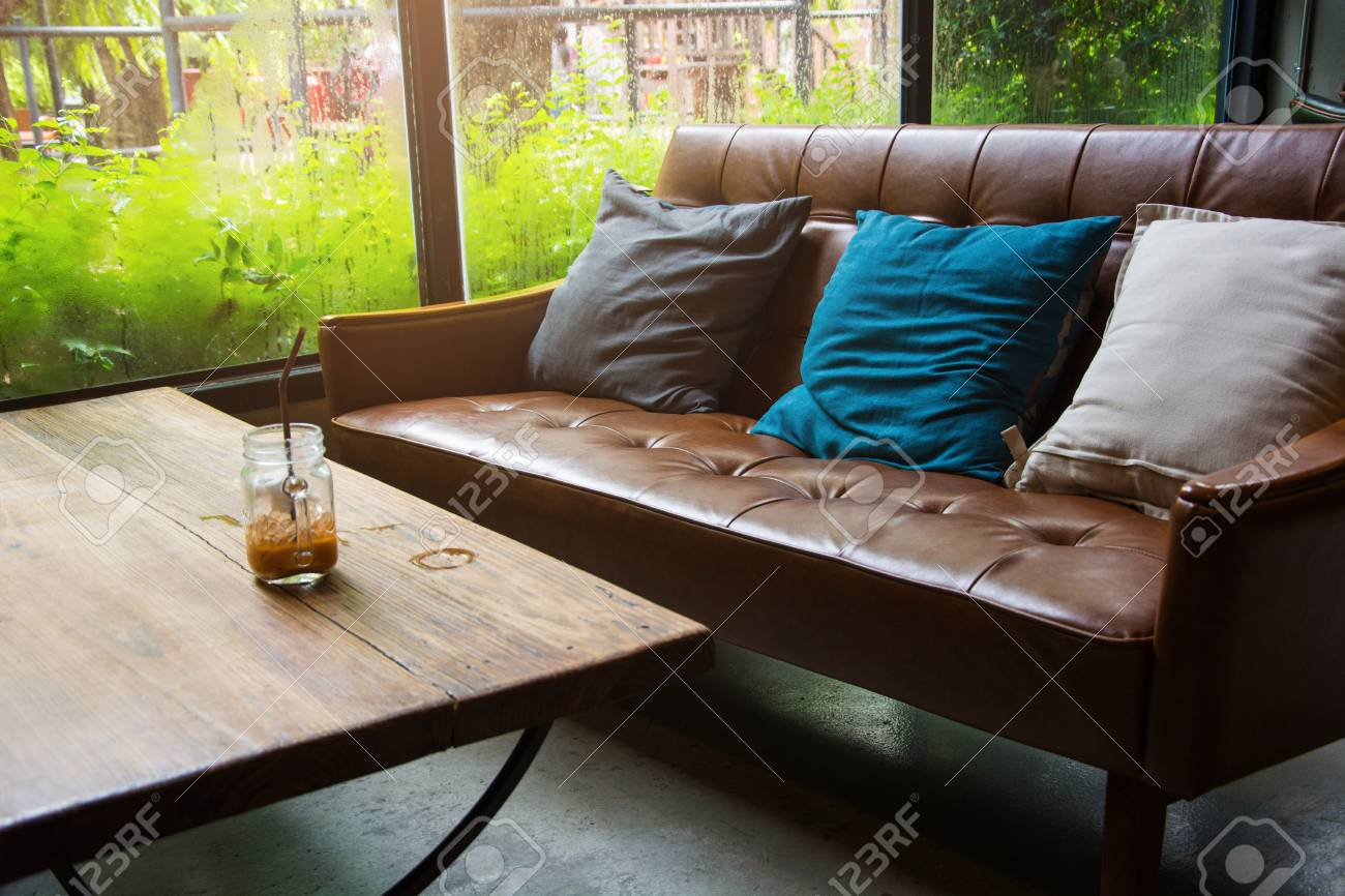 Leather Sofa With A Glass Of Water On A Wooden Table In A Coffee Shop.