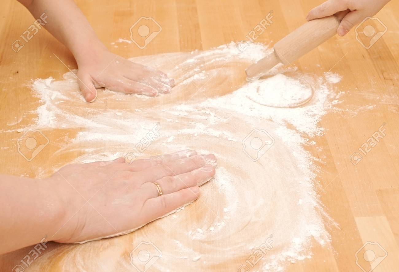 A child is helping mom to knead the dough for baking Stock Photo - 11599308