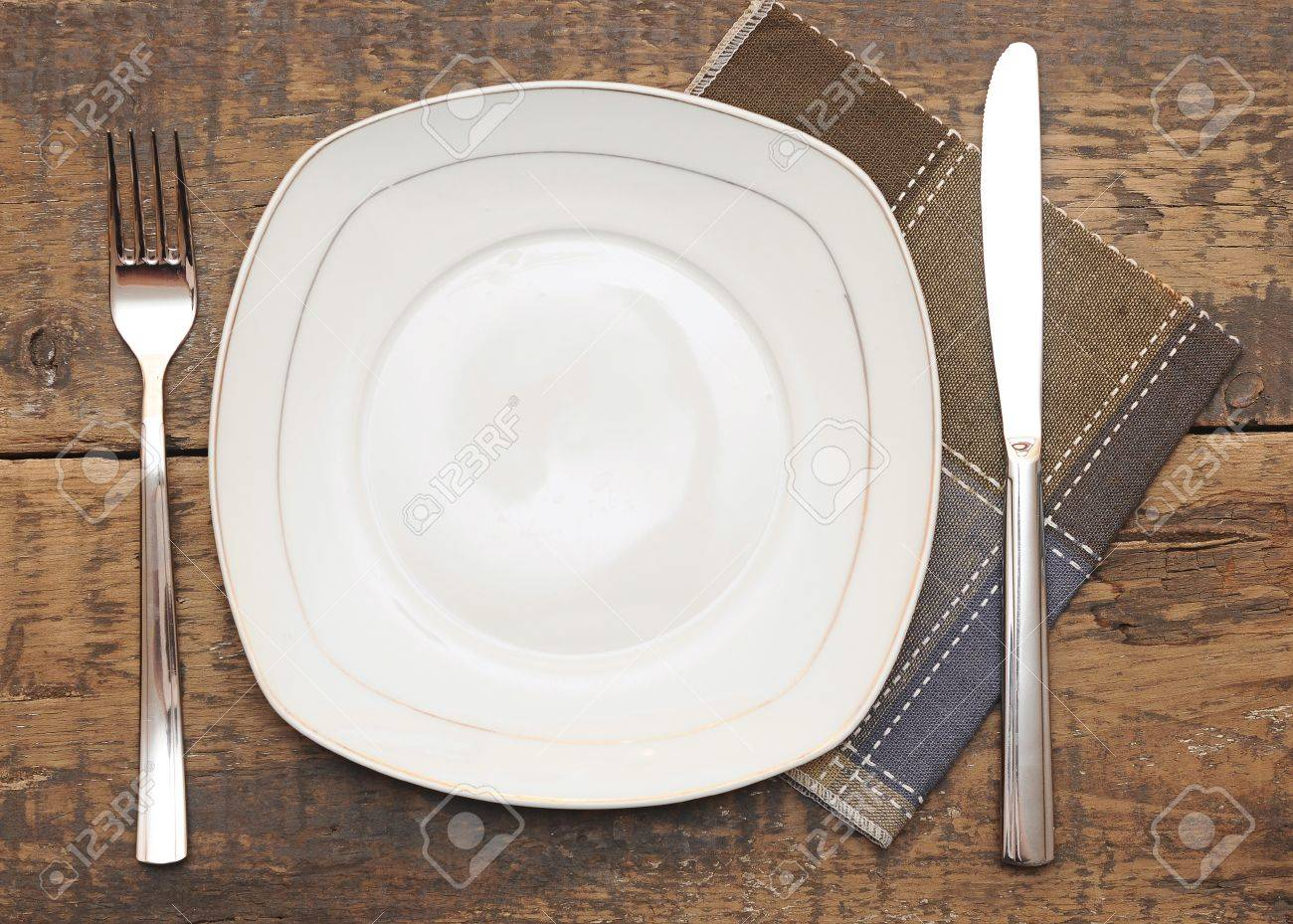 Empty dish, knife and fork and brown napkin on wood table Stock Photo - 12893059