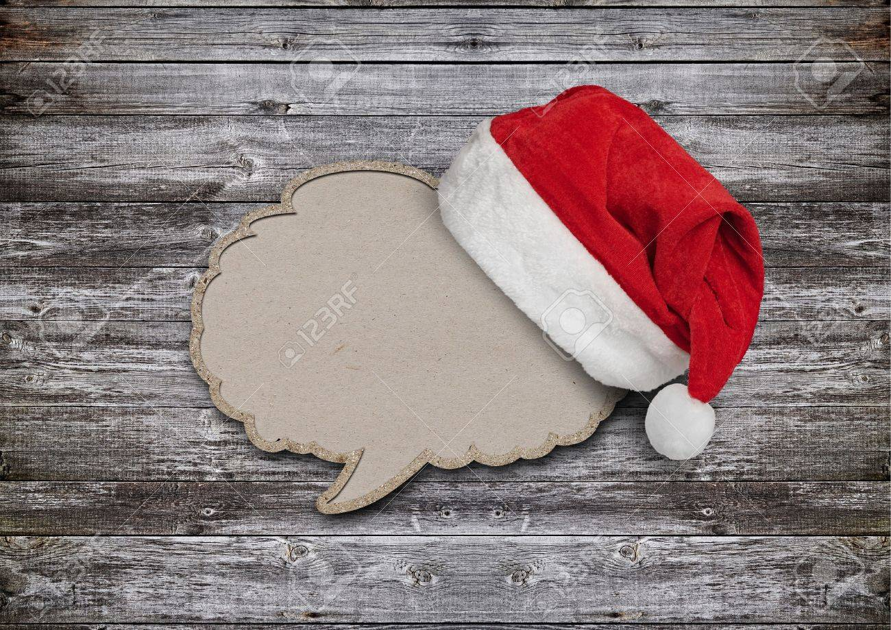 blank recycled paper speech bubble with santa hat on wood background