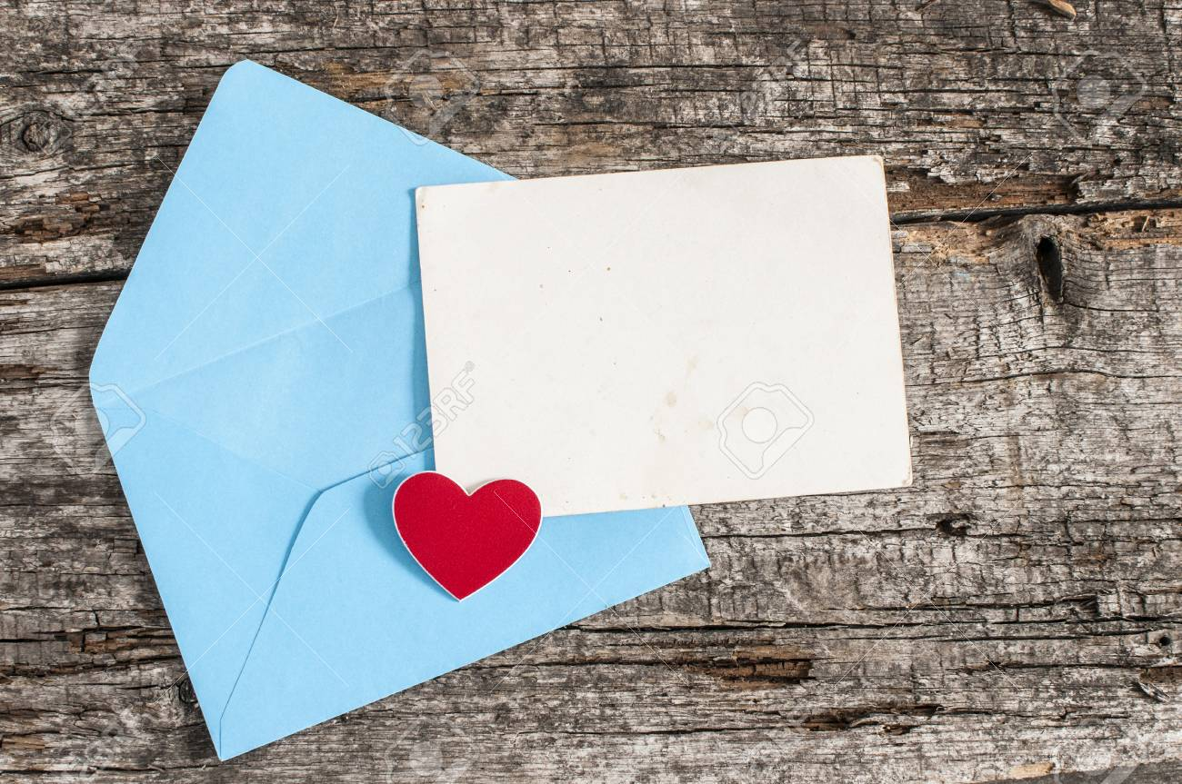 Blank card and envelope on old wooden background