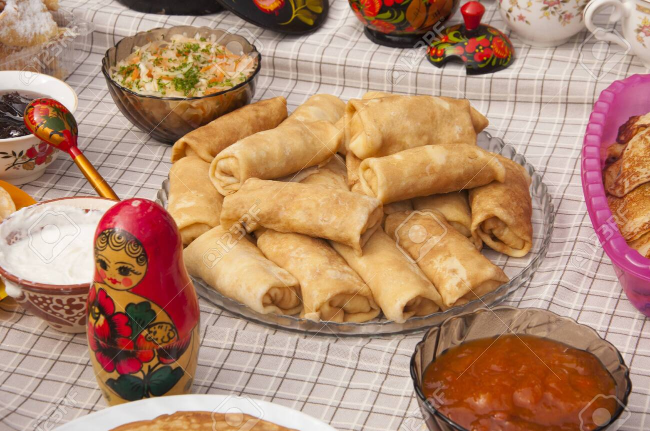 Stack of russian pancakes blini and traditional wooden dolls matrioshka. - 122828643