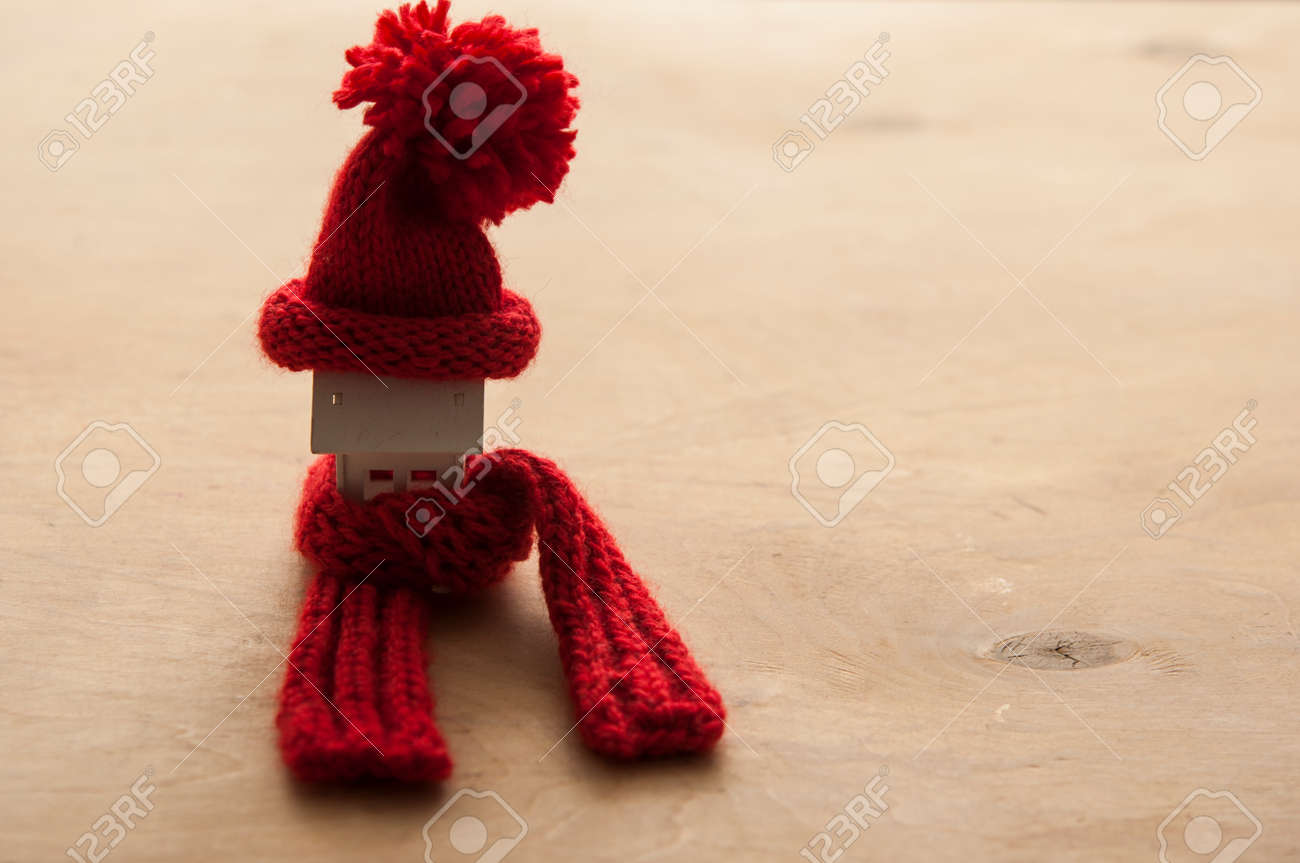House model with knitted hat and scarf on table against white background. Heating concept - 133411643