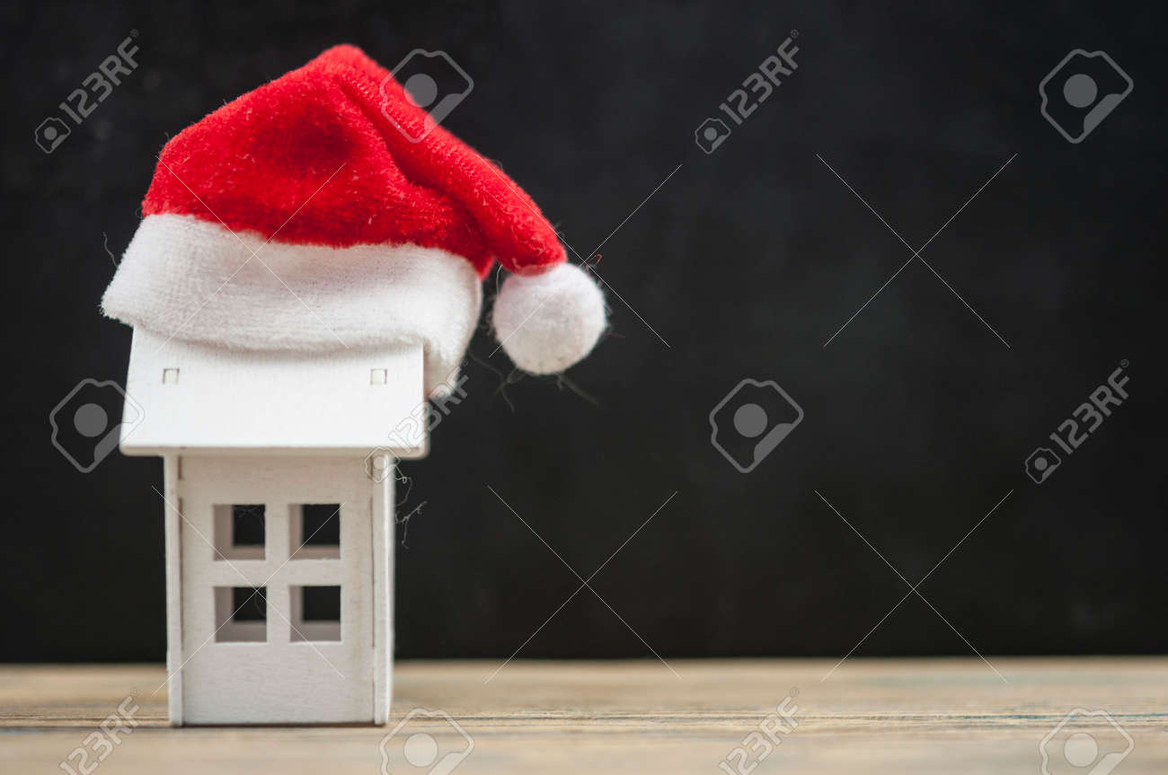 Santa hat with miniature house model on wooden table - 157979865