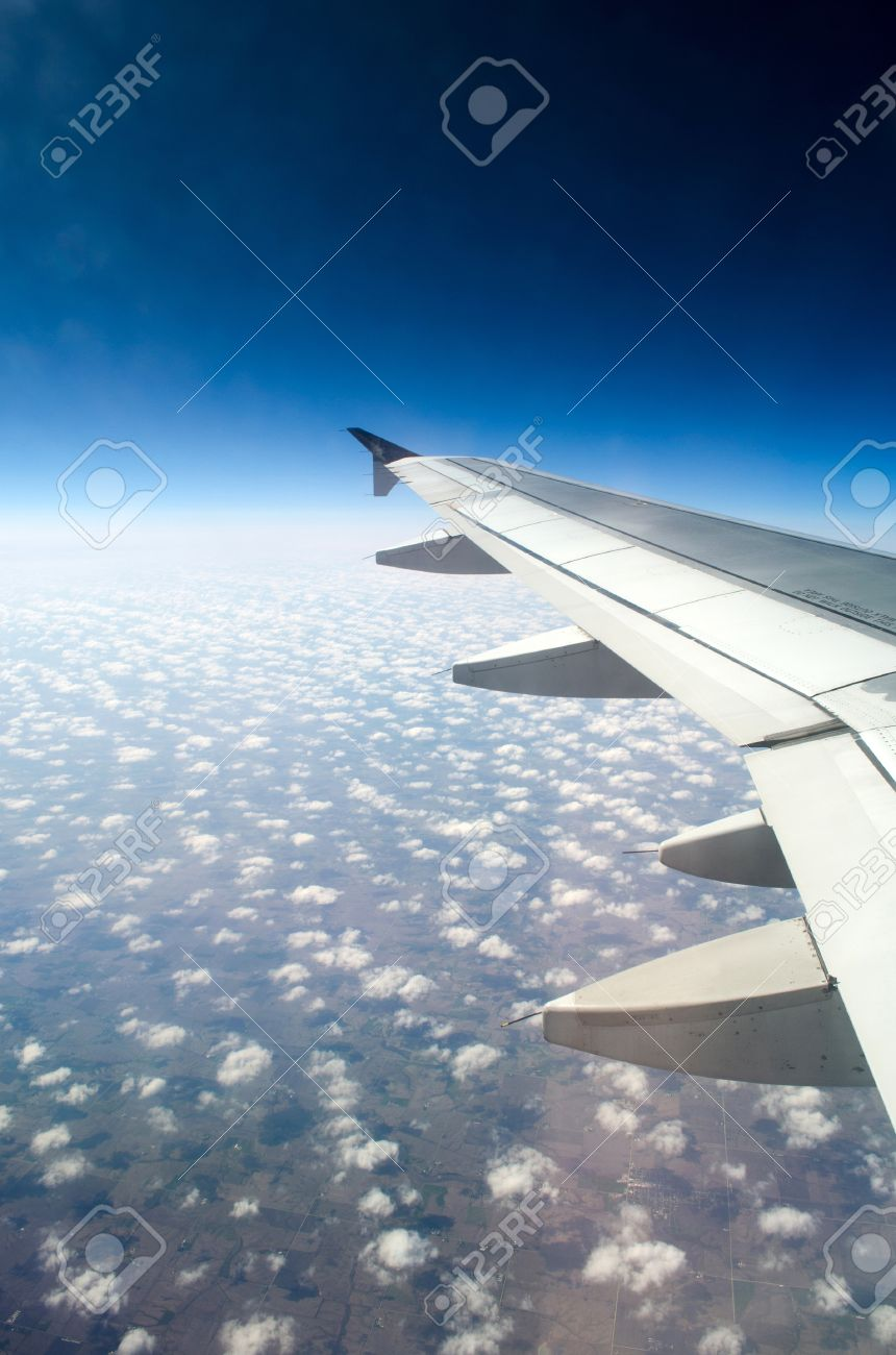 clouds out of an airplane window and wing of plane stock photo