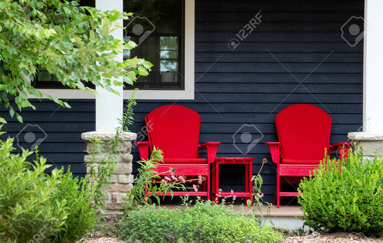 Stock Photo   Two Red Adirondack Chairs Sit On A Front Porch Beach House  Waiting For Someone To Sit Back And Relax