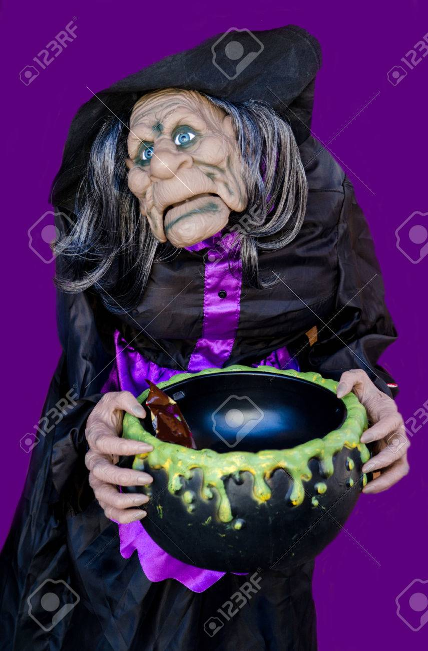 a scary animated witch on a purple background, holds a black.. stock