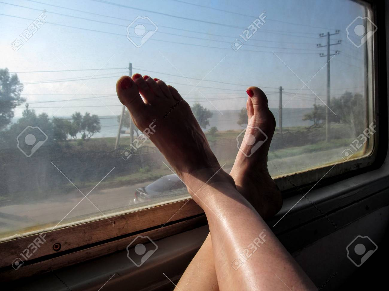 Stock Photo The Concept Of Travel With Convenience Female Feet In The Train Window Window Of Public Transport Womens Legs With A Red Pedicure