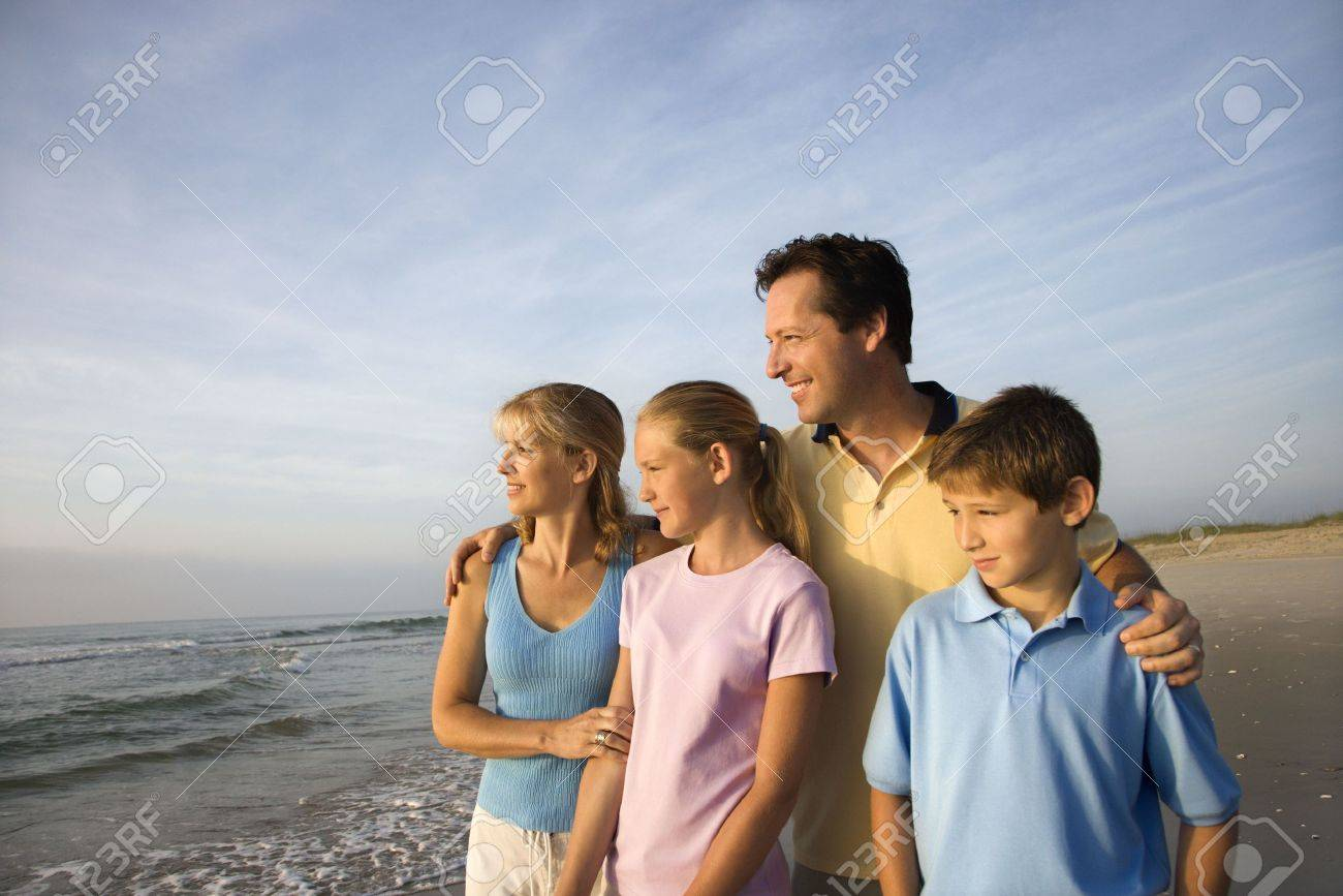 Portrait of Caucasian family of four posing on beach looking at ocean. Stock Photo - 1762020