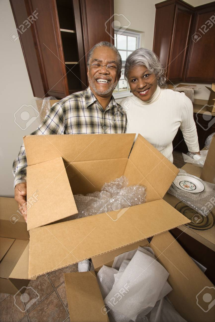 Portrait of middle-aged African-American couple with moving boxes in kitchen. Stock Photo - 1797463