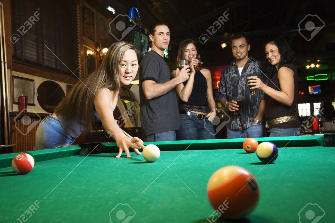 Stock Photo - Young asian woman preparing to hit pool ball while playing  billiards. 9eeb74a81e