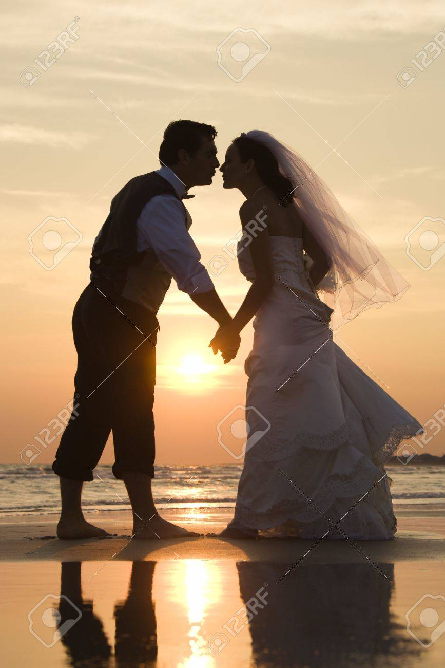 Caucasian mid-adult bride and groom holding hands and kissing barefoot on beach at sunset. Stock Photo - 1795514