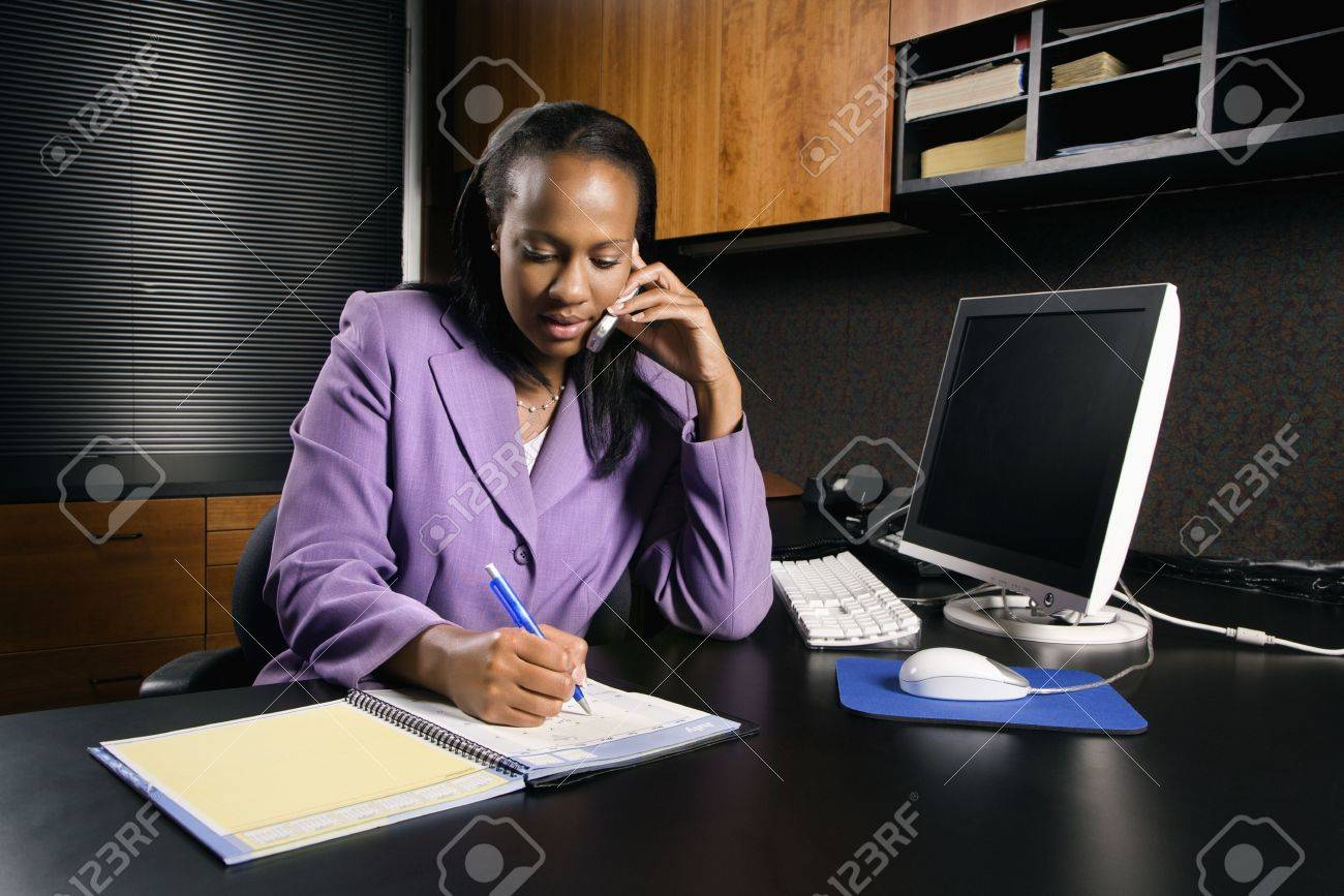 African-American young adult business woman talking on cell phone and writing in planner in office. Stock Photo - 1796970
