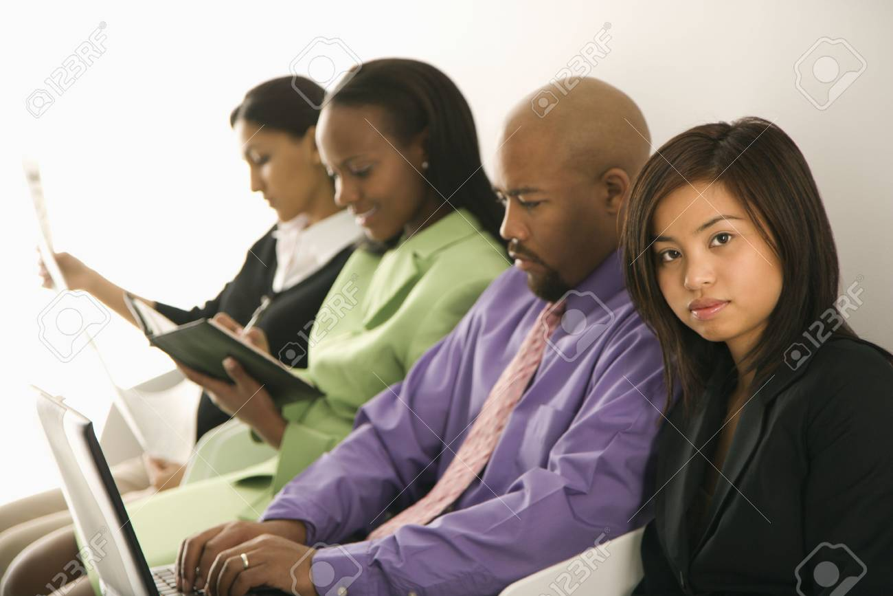 Vietnamese businesswoman sitting looking at viewer with others in background. Stock Photo - 1796858