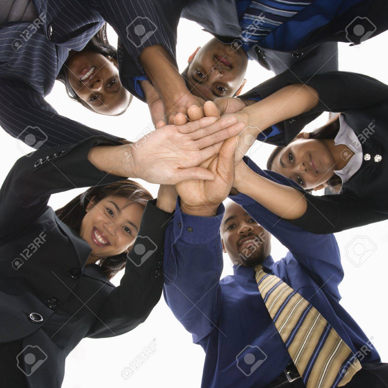 Low angle portrait  of multi-ethnic business group of men and women with hands in huddle. Stock Photo - 1796866